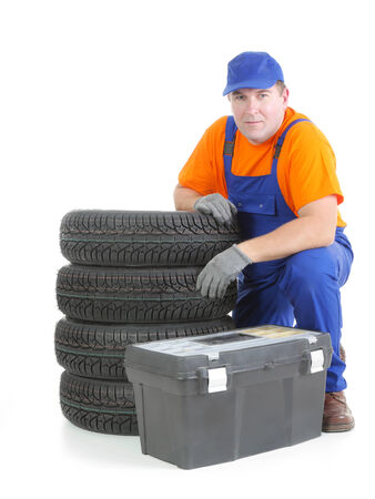 Mechanic wearing blue coveralls and orange t-shirt posing by pile of four new car tires and toolbox shot on white photo