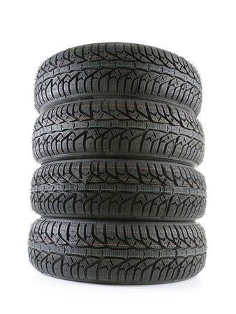 winter tires: Pile of four winter car tyres on white