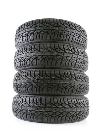 Pile of four winter car tyres on white photo