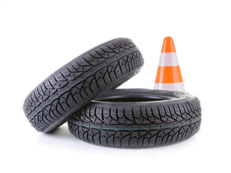 winter tyre: Two winter car tyres and road cone shot on white