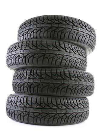 Pile of four winter car tyres shot on white photo