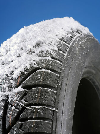 Closeup of winter car tyre covered with snow shot on blue background photo