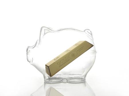 Gold bar inside glass piggybank shot on white background Stock Photo