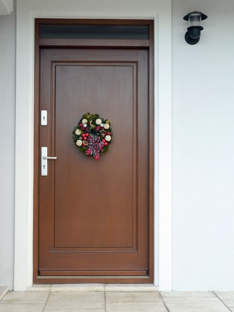 Christmas wreath with decorations and ribbon bow attached to the wooden door photo
