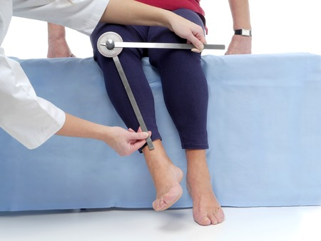 range of motion: Physiotherapist measuring active range of motion of older patients lower limb using manual goniometer Stock Photo