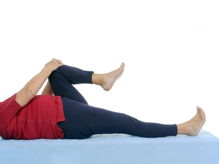 Older patient performing funtional test of hip joint contraction lying on bed photo