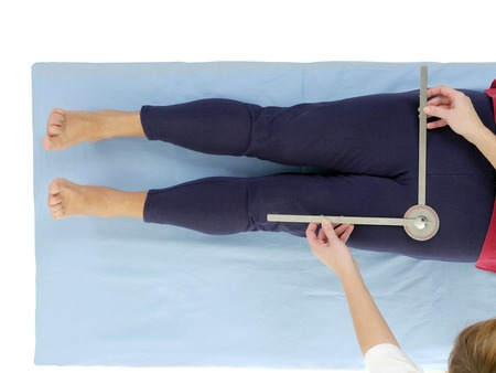 Physiotherapist measuring active range of motion of older patients lower limb using manual goniometer Stock fotó
