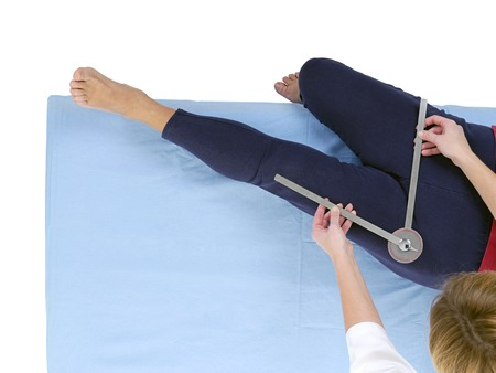 Physiotherapist measuring active range of motion of older patients lower limb using manual goniometer photo