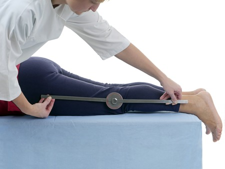 physical test: Physiotherapist measuring active range of motion of older patients lower limb using manual goniometer Stock Photo