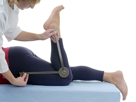 Physiotherapist measuring active range of motion of older patients lower limb using manual goniometer Stock Photo