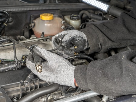 replacing: Auto mechanic replacing broken Diesel glow plug wire in car diesel engine compartment