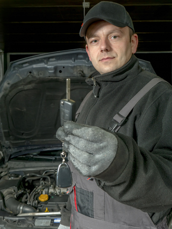 repaired: Auto mechanic holding a car key of the repaired car waiting to be handed over to the customer Stock Photo