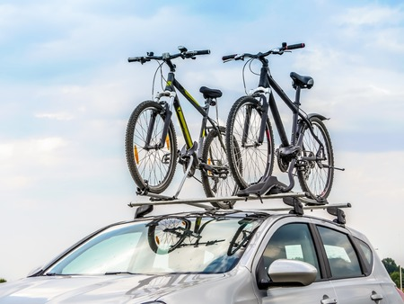 racks: Passanger car with two bicycle mounted to the roof