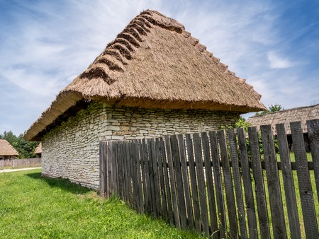 thatched: Farmstead with thatched cottage and picket fence shot against blue sky