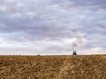 harrowing: Farm tractor harrowing arable field Stock Photo