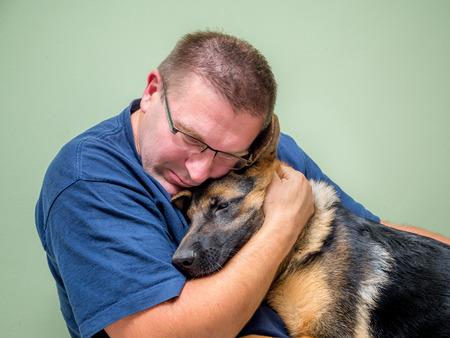 sad person: Young man hugging and consolating his dog