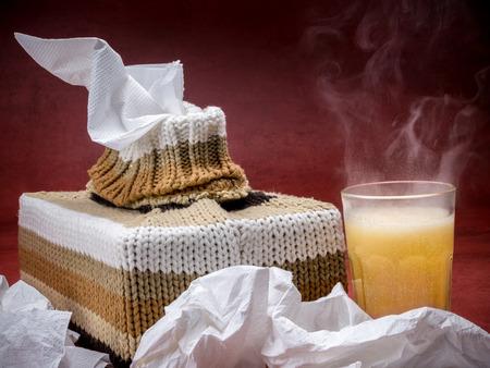 effervescent: Tissue box in knit encasement and hot flu medicine drink over dark red background Stock Photo