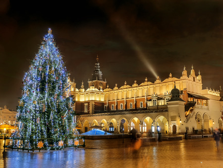 Giant christmas tree illuminated at night standing next to historical Cloth Hall on the Main Market Square in Krakow, Poland