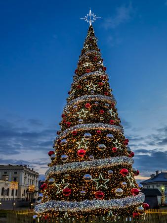 Giant outdoors Christmas tree illuminated at night