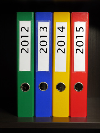 Four color binders organized by year 2012 to 2015 placed on bookshelf photo