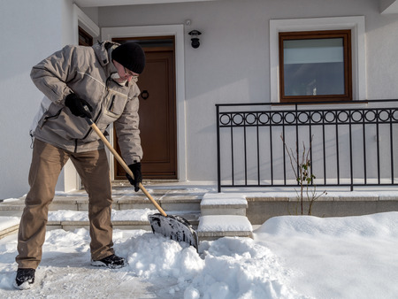 Man clearing path to his house of snow with shovel after heavy snowing Archivio Fotografico