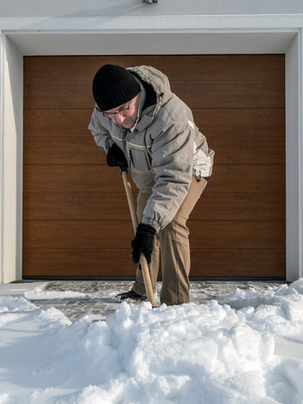 Man clearing driveway of snow with shovel after heavy snowing