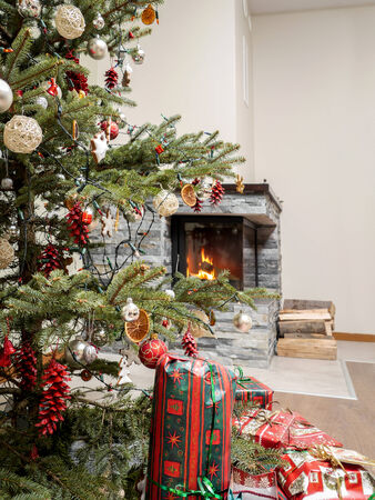 Christmas tree with christmas presents by the lit fireplace photo