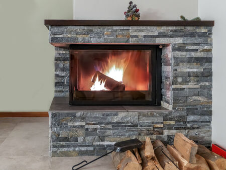 Stone fireplace with lit firewood Stock Photo