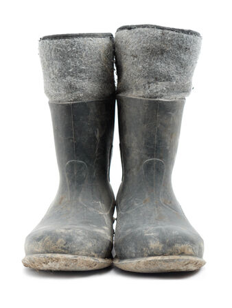Dirty rubber-soled felt insulated boots shot over white photo