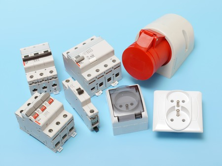 disconnecting: Electrical circuit breakers, main disconnet, power socket and 230 Volt wall sockets shot over blue