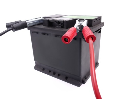 12v: Car battery with two jumper cables clipped to the terminals shot over white