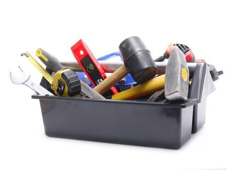 Caja de herramientas de plástico negro con las herramientas sobre fondo blanco