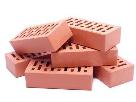materiales de construccion: Pila de ladrillos perforados sobre el fondo blanco Foto de archivo