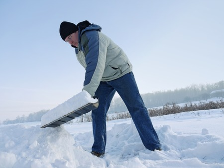 plows: Man plowing his backyard with shovel after heavy snowing