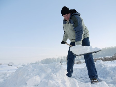 Man clearing path from snow with snow shovel after heavy blizzard