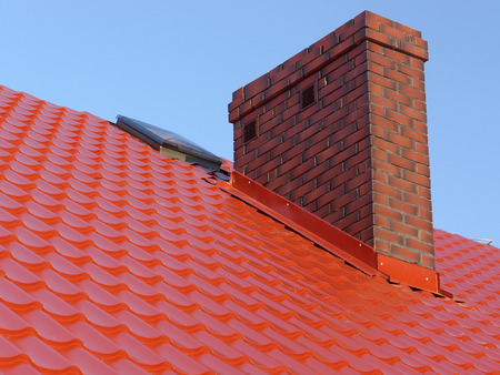 Closeup of red roof metal covering with brick-made chimney Standard-Bild