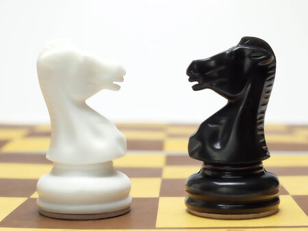 chess knight: Black and white chess knights standing face to face over white background Stock Photo