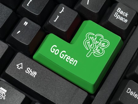 Closeup of computer keyboard key in green color with Go Green phrase and tree symbol