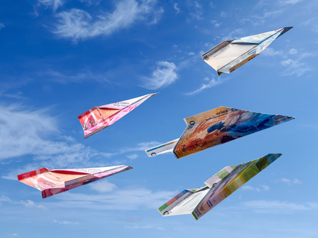 Swiss Franc banknotes as toy planes rising high in the sky Stock Photo