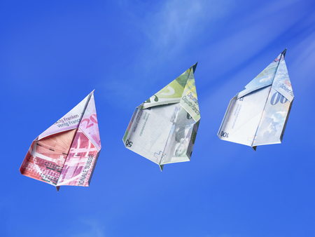 business metaphore: Swiss Franc banknotes as toy planes rising high in the sky Stock Photo