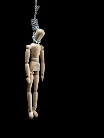 hanged: Wooden dummy being hanged by the neck on the noose over black background