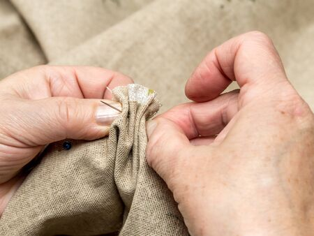 stitching: Closeup of senior womans hands basting linen border with needle and thread Stock Photo