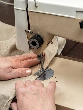 stitching machine: Closeup of senior womans hands sawing linen border with sewing machine Stock Photo