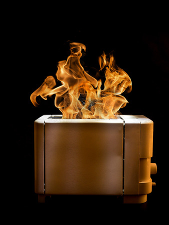 burning: Toaster with two slices of toast caught on fire over black background Stock Photo