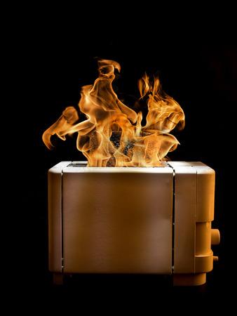 fogatas: Tostadora con dos rebanadas de pan tostado se incendi� sobre el fondo negro Foto de archivo