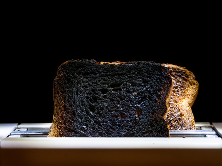 burnt toast: Two burnt toast slices sticking out of toaster over black background