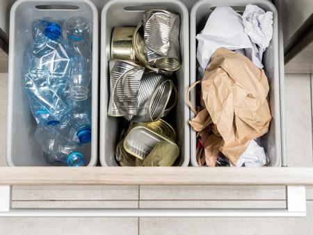 reciclaje de papel: Tres contenedores de basura de plástico en mueble de cocina con basura segregada hogar - botellas de PET, papel y latas de metal disparó desde arriba