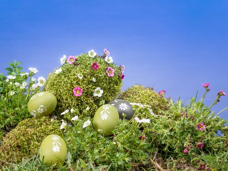 giant easter egg: Easter eggs scattered in the grass and giant moss-grown egg with fresh spring flowers over blue sky Stock Photo