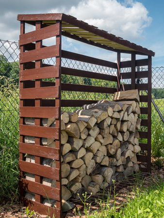 woodshed: Woodshed with arranged chopped firewood Stock Photo
