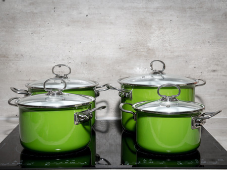 induction: Four green enamel stewpots on black induction cooker Stock Photo